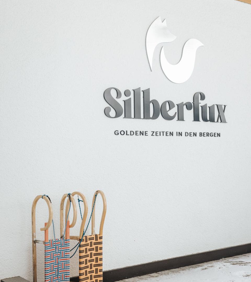 Silberfux Hauswand im Winter mit Schlitten